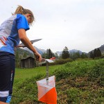 Female Orienteering competitor running up to a flag
